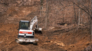 A Bobcat E50 excavator digs along a trail at Windrock Bike Park.