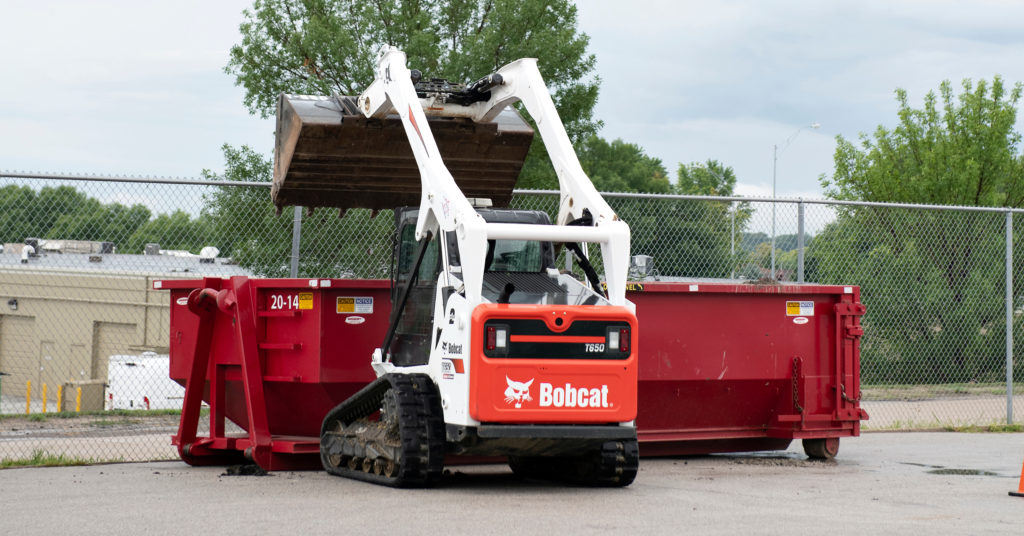 Chris Menn dumps a load of broken concrete into a rolloff container using a T770 compact track loader