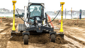 A T650 compact track loader grades a construction site using a 3D grade control system.