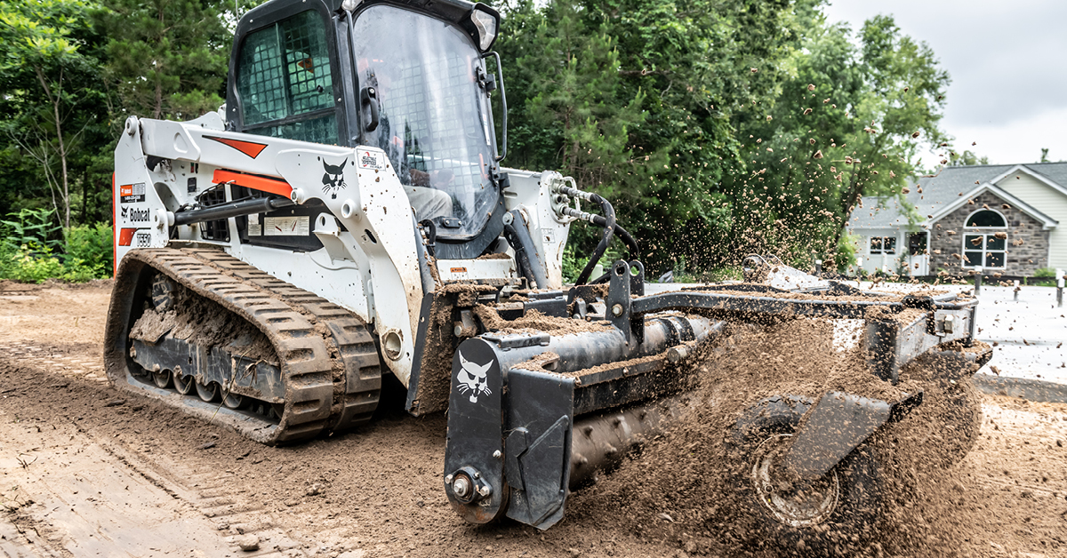 A T550 compact track loader uses a soil conditioner to prepare ground.