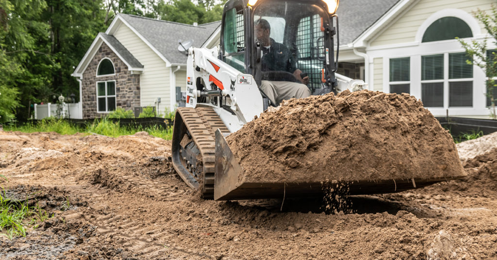 An operator moves dirt with a compact track loader on a residential construction site.