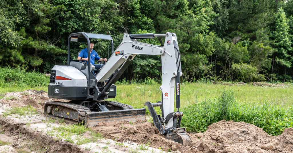 An operator uses an E42 compact excavator with a long arm to dig.