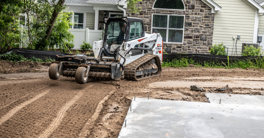A T550 compact track loader uses a soil conditioner to prepare ground at a residential construction site.