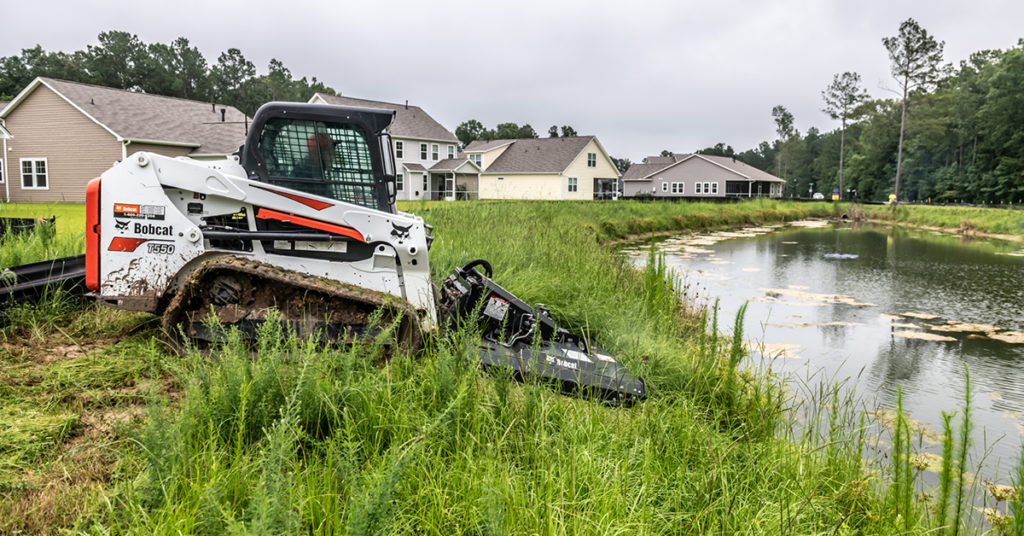 A T550 compact track loader uses a Brushcat rotary cutter to mow overgrown grass surrounding a pond.