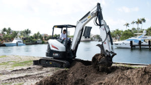 Bobcat mini excavator with an extendable arm works beside a Florida canal