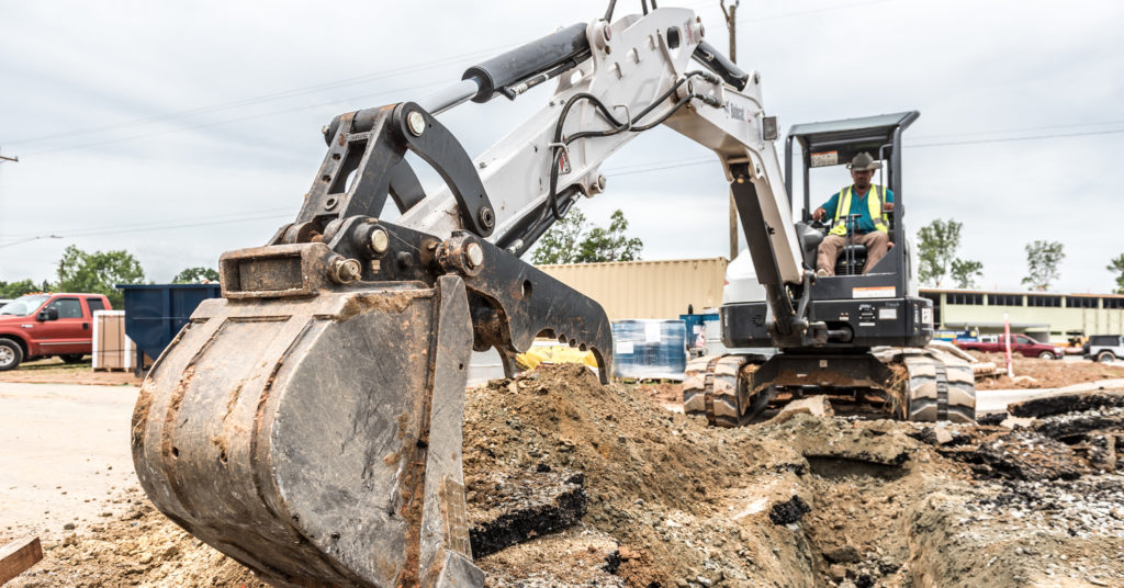 Compact excavator digging footings for restaurant construction