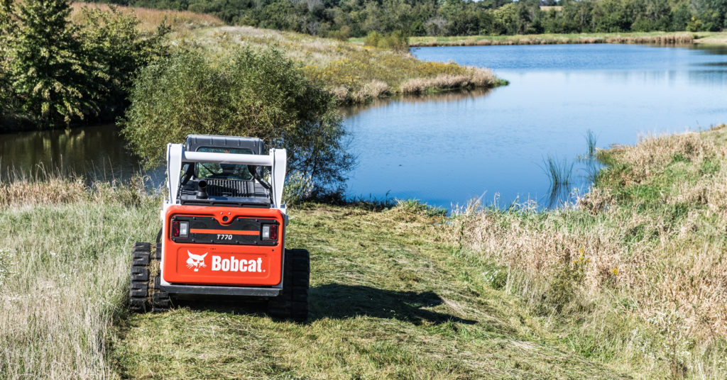 Bobcat compact track loader removes brush