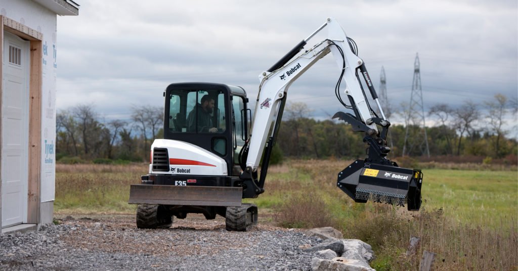 A Bobcat E35 compact excavator clears brush with a flail mower attachment
