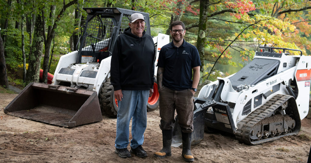 George Lohmiller and Anthony Guadagno stand next to the company's 751 skid-steer loader and MT85 mini track loader.