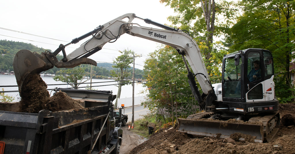A Bobcat E85 mini excavator loads a full bucket of dirt into a dump truck.