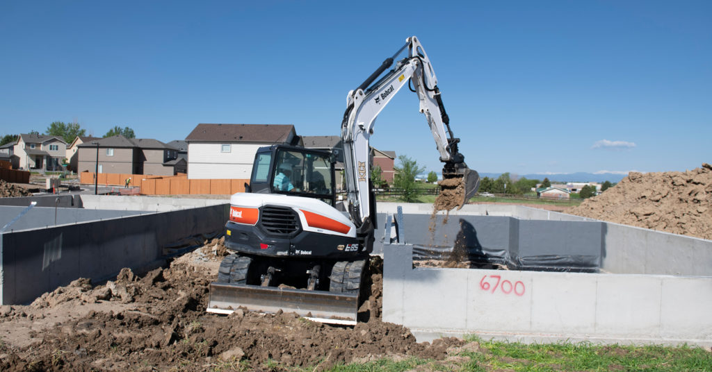 Bobcat excavator with plate attachment operates near Bobcat loader.