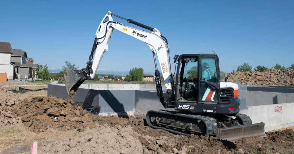 Bobcat excavator digs with bucket attachment.