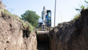 Bobcat E35 digs a deep trench for water and sewer lines.