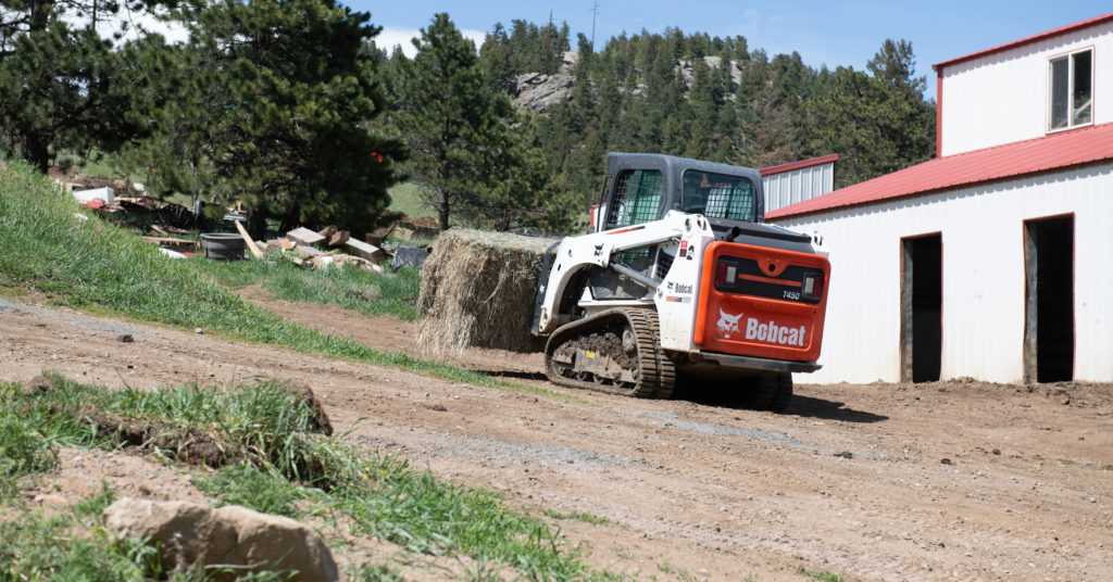 A Bobcat compact track loader carries a hay bale up an incline.