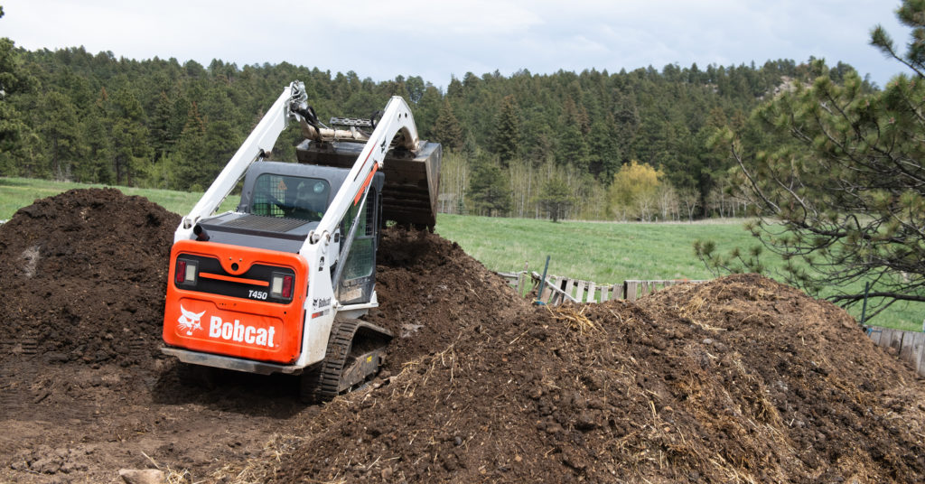 A Bobcat loader uses a bucket attachment to dump compost into a pile.