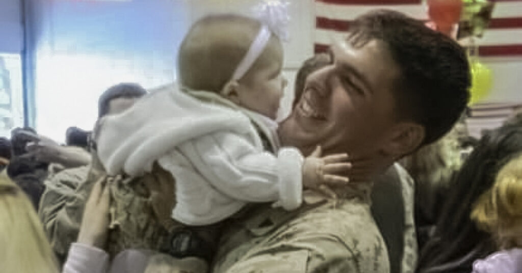 U.S. Marine Peter Freundschuh holds his infant daughter after military deployment.