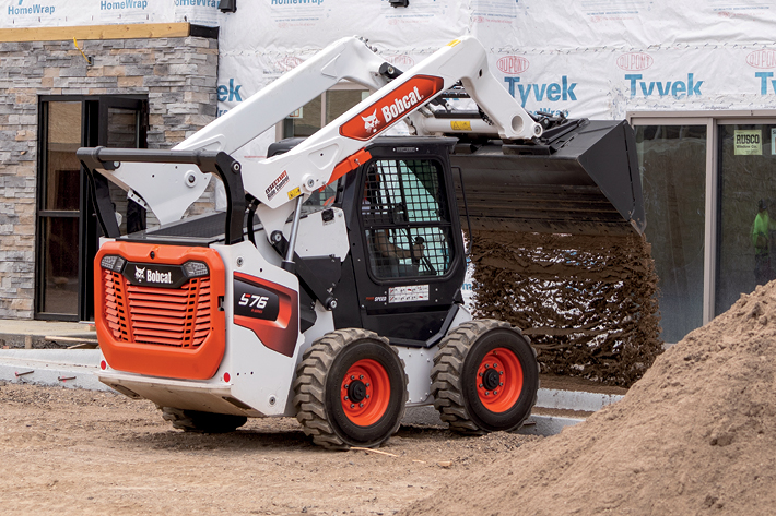 Construction Worker Using a Bobcat Compact Loader to Dump Dirt at a Jobsite