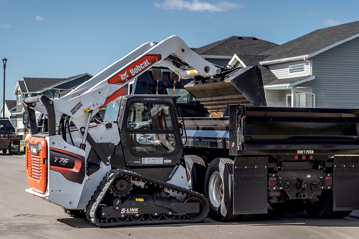 Construction Worker Using a Bobcat Compact Loader to Dump Materials onto a Trailer