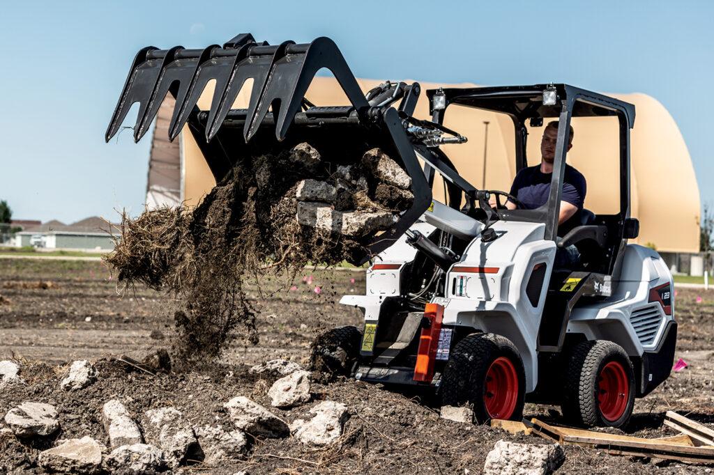 Operator Moves Rock And Dirt Using Grapple Attachment On Small Articulated Loader