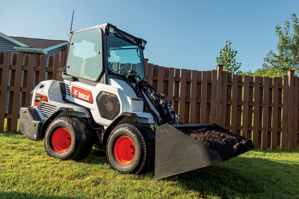 Operator Hauls Dirt On Established Landscape Using Bucket Attachment On Small Articulated Loader