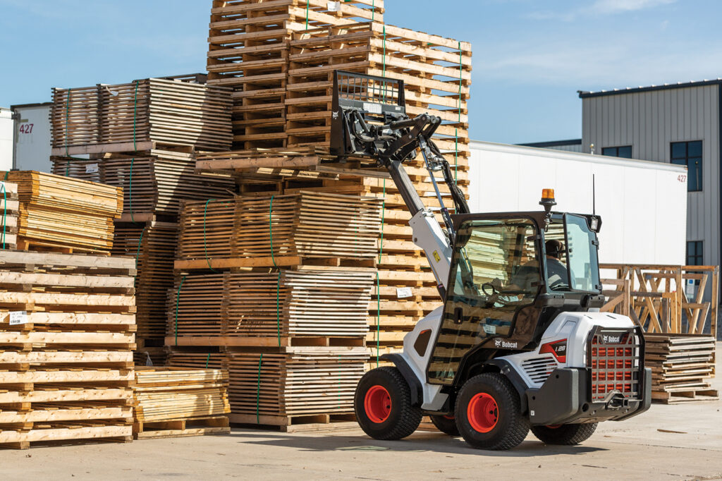 Operator Transports Pallets Using Pallet Fork Attachment On Small Articulated Loader