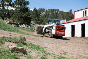 Livestock Farmer Moves Hay Using Bale Fork Attachment On Compact Track Loader.