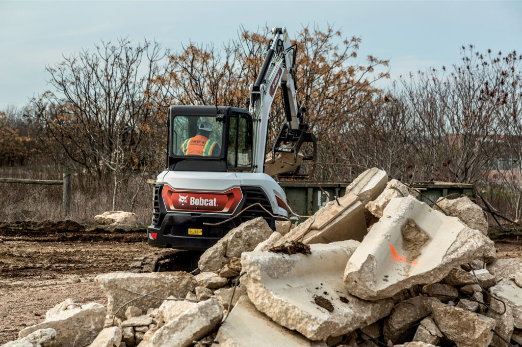 R2-Series Compact Excavator Grabs a Piece of Concrete With a Bucket and Hydraulic Clamp