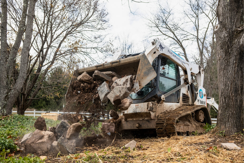 A T650 Compact Track Loader Dumps Rock At Jobsite For Building Retaining Walls