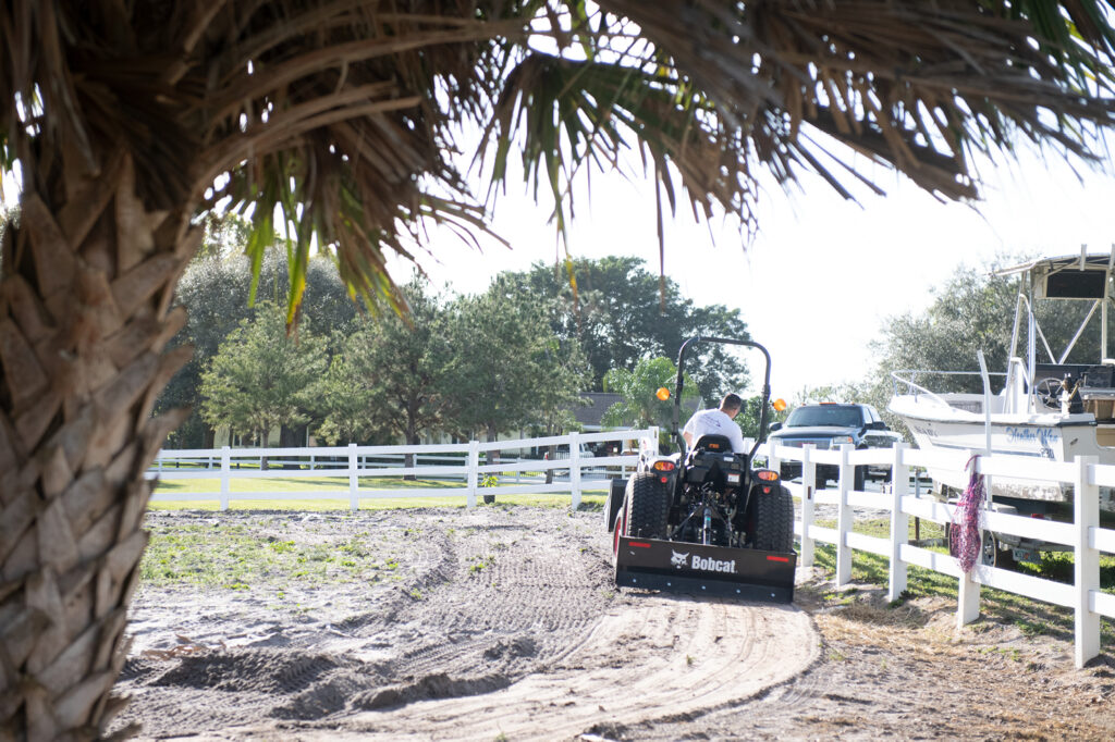 Joe D'Amico Grades The Riding Arena With A Box Blade Implement On A Compact Tractor