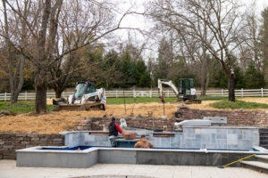Workers Build A Fish Pond And Retaining Wall At Residential Jobsite