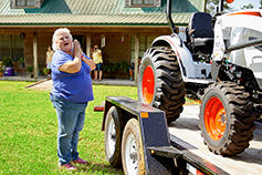 Kristine Gazes At Her New Compact Tractor On The Delivery Trailer