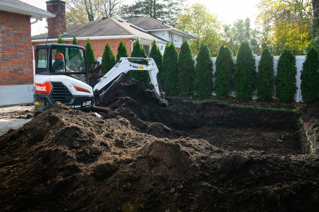 Bobcat E32 Mini Excavator Digs Hole For Backyard Pool Installation