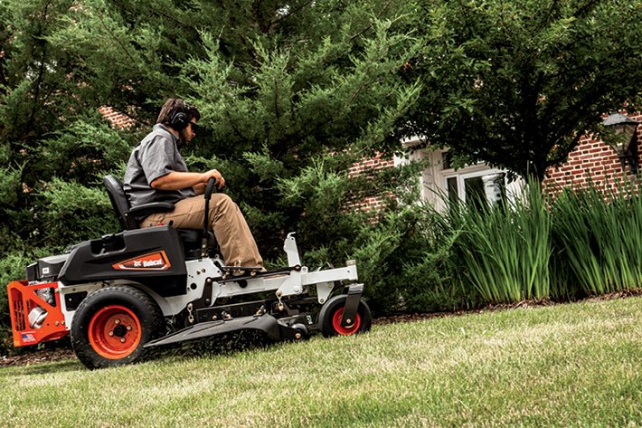 Operator Uses Bobcat Mower To Mow Around Residential Landscaping Beds