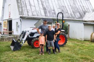 Acreage Owners Stand In Front Of Their Bobcat Compact Tractor