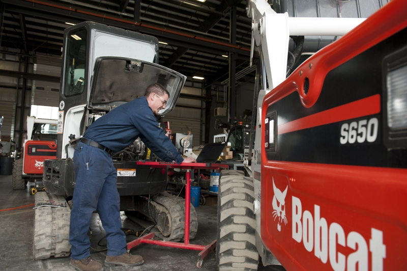 A service technician works on his laptop next to the Bobcat S650 skid-steer loader he's repairing