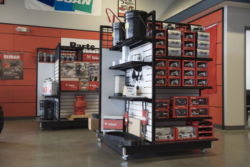 Two display shelves of stacked Bobcat parts and merchandise inside Finke Equipment's showroom