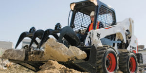 Bobcat skid-steer loader with grapple on construction site