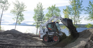 Bobcat S570 dumps dirt with mountains and lake in background.