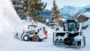 Two skid-steer loaders using snow blowers in the mountain town of Mammoth Lakes