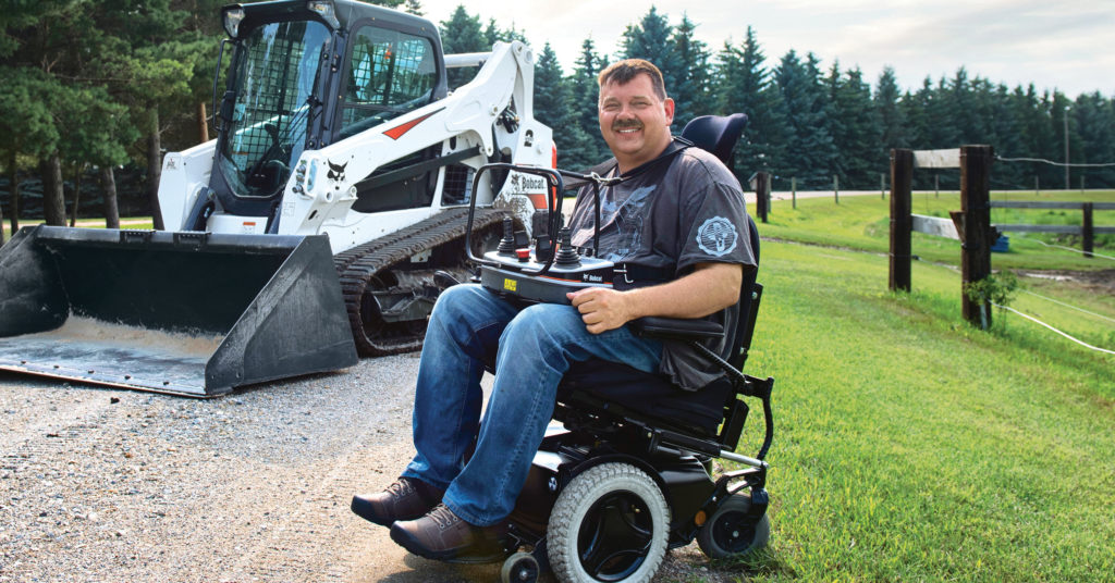 Trevor Brown sits in his wheelchair near his Bobcat T595 compact track loader holding the controls to the radio remote control system.