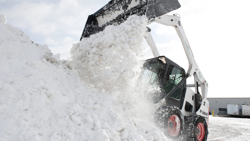 A Bobcat S650 skid-steer loader pushes snow at an Omaha parking lot.