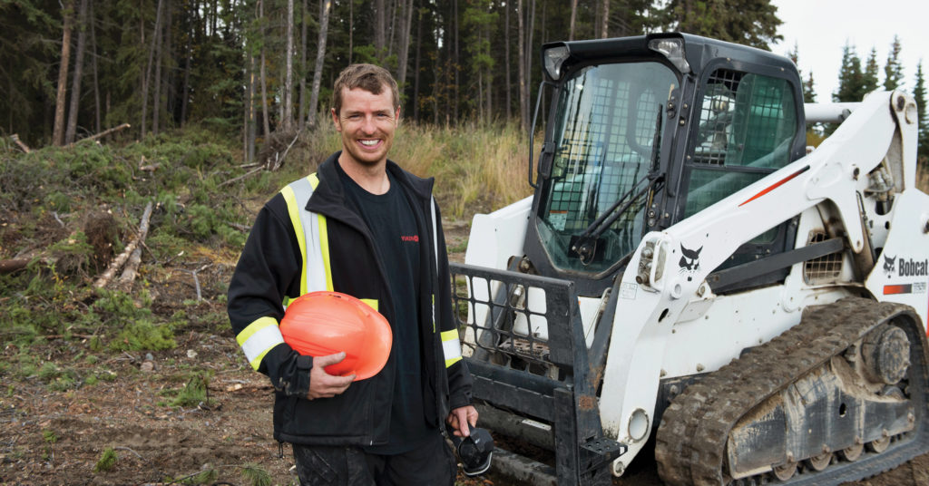 Sean O'Donnell stands next to his Bobcat T650 compact track loader at a wooded jobsite.
