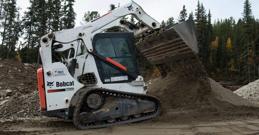 Sean O'Donnell dumps dirt from the bucket of his Bobcat T650 compact track loader.