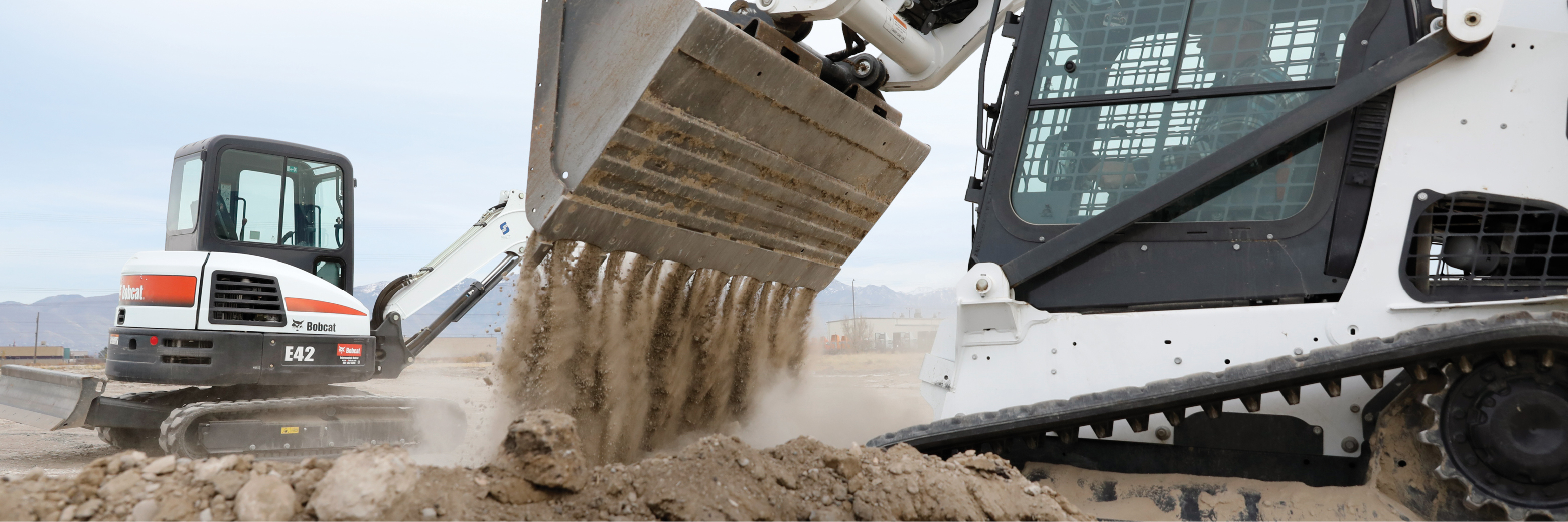 Todd Sharp dumps dirt out of the bucket of his Bobcat T650 compact track loader.