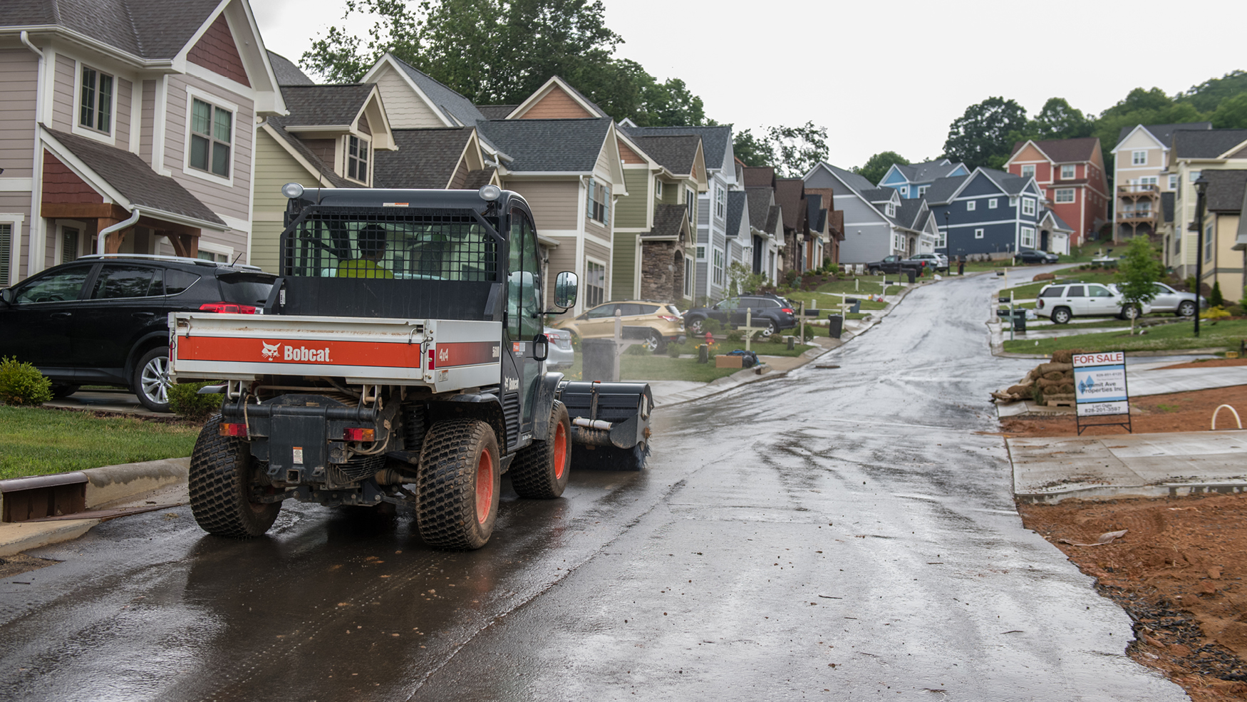 Toolcat 5600 sweeps dirt from the street near a recently graded yard.