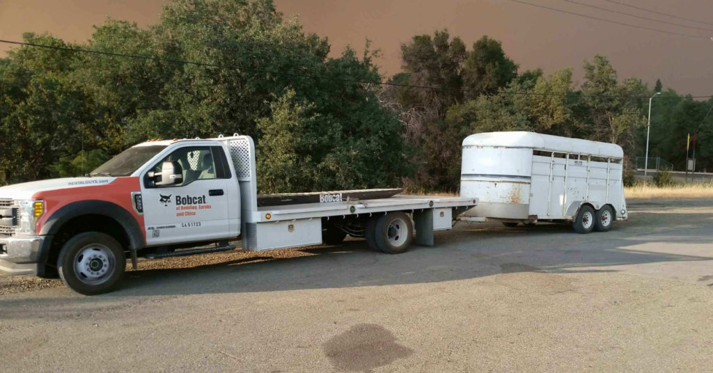 A flatbed truck and horse trailer stand ready to evacuate animals during the Carr wildfire.