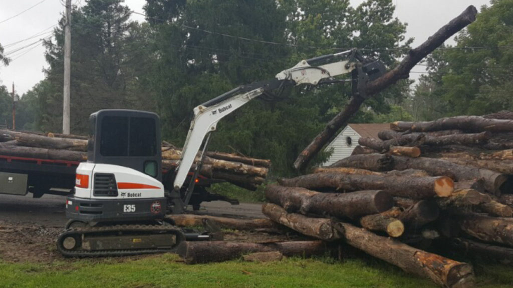 Bobcat E35 excavator lifting and moving logs