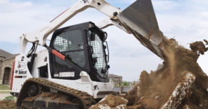 A Bobcat T590 compact track loader dumps dirt at an Alterra jobsite