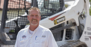 Randy Henry stands in front of his Bobcat T590 compact track loader