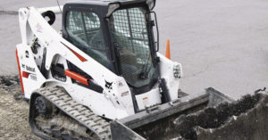 Bobcat T650 compact track loader moving pieces of concrete
